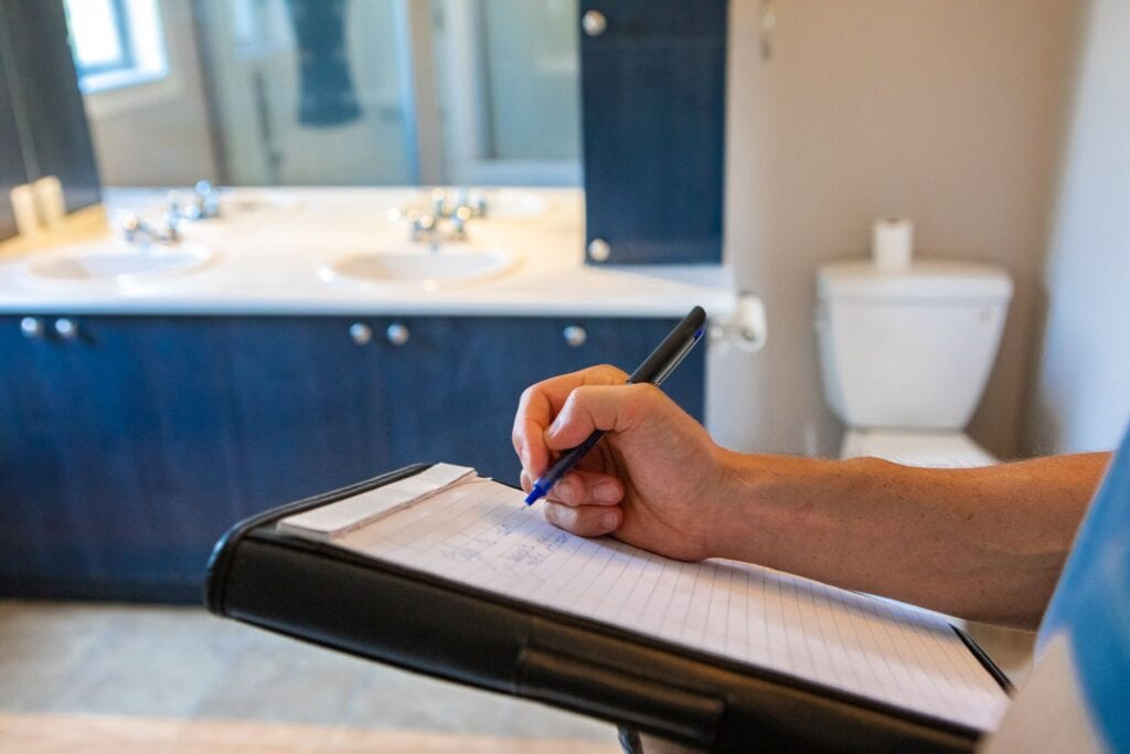 hand of a man using a pen and notepad to jot down defects and problems during an indoor home inspection