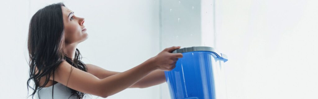Worried young woman holding bucket under water drops